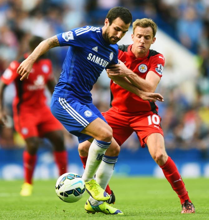 Chelsea's Cesc Fabregas (left) tries to get the ball past Andy King of Leicester City