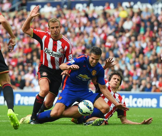 Robin van Persie of Manchester United is tackled by Lee Cattermole (L) and Santiago Vergini of Sunderland during the Barclays Premier League match