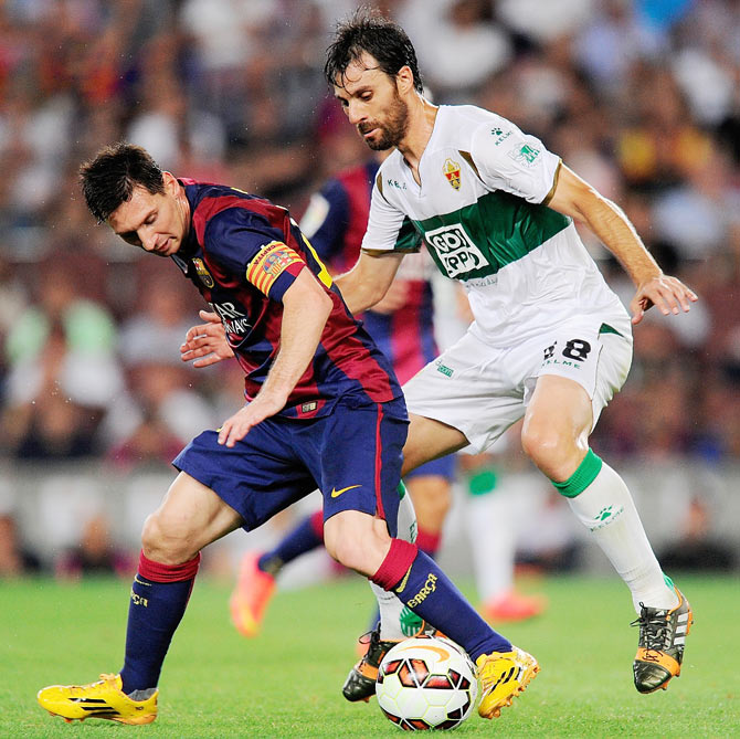 Lionel Messi of FC Barcelona shields the ball from Sergio Pelegrin of Elche FC during the La Liga match on Sunday