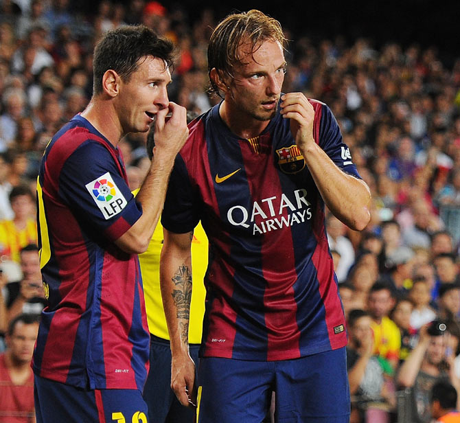 Barcelona's Ivan Rakitic (right) consults with teammate Lionel Messi before taking a freekick during the La Liga match on Sunday