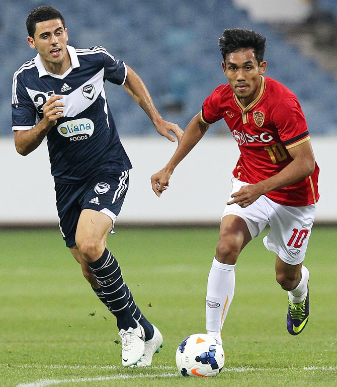 Teerasil Dangda of Muangthong United (right) runs past a defender of Melbourne Victory during their AFC Champions League playoff match at Skilled Stadium in Melbourne on February 15, 2014