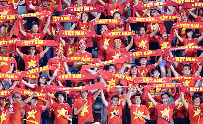 Vietnamese fans cheer during the AFC match