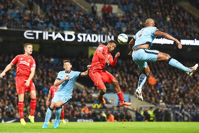 Daniel Sturridge of Liverpool competes with Vincent Kompany of Manchester City