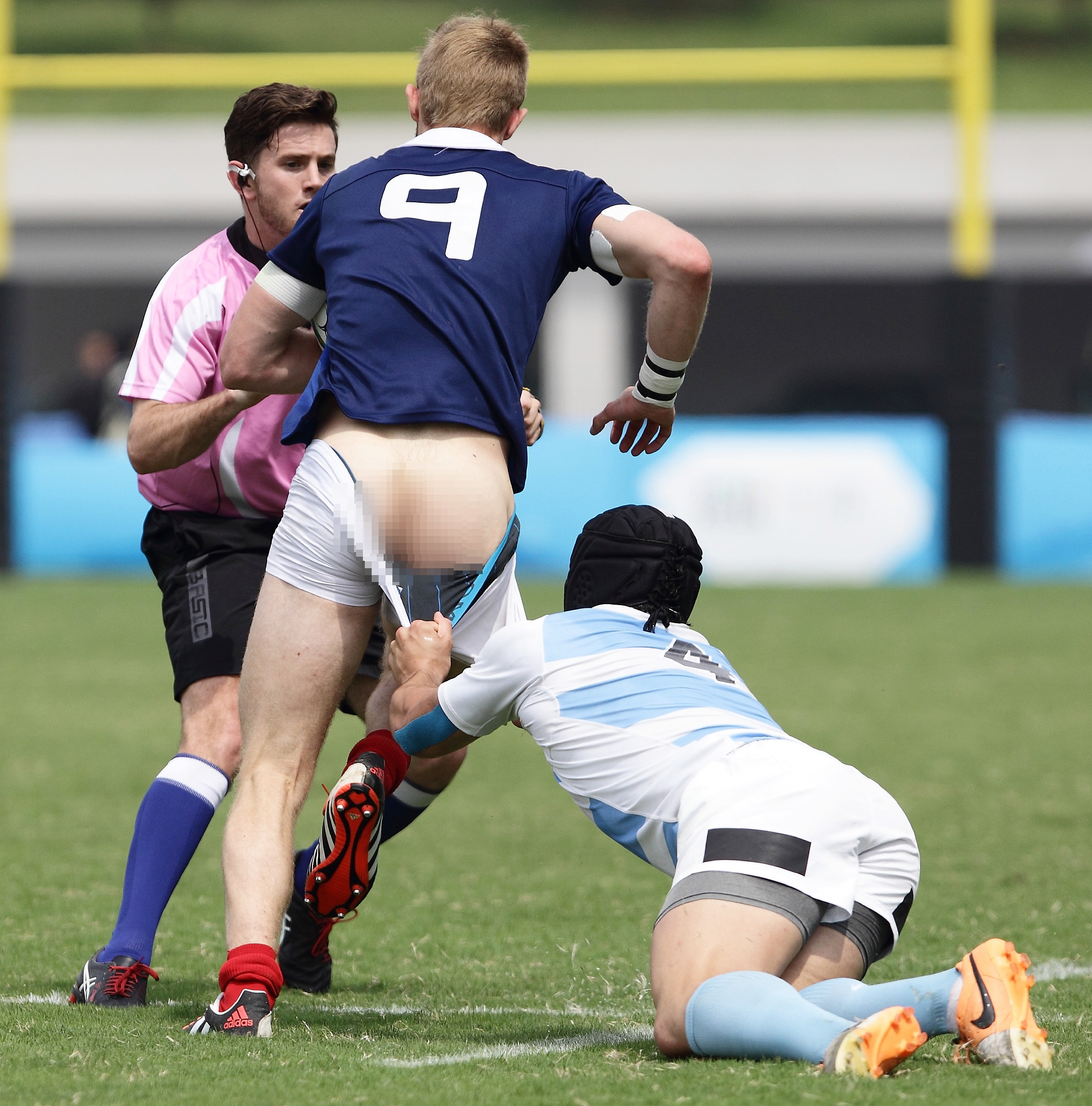 Conil Ignacio of Argentina pulls down Faraj Fartass of France during the Rugby Sevens final on day four of the Nanjing 2014 Summer Youth Olympic Games at the Olympic Sports Park