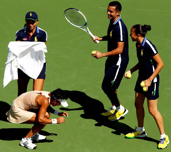 Ball people attempt to catch a honey bee in front of Kimiko Date-Krumm of Japan during   her women's singles first round match match against Venus Williams of the United States