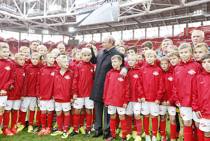 Russian President Vladimir Putin talks to young soccer players during a visit to Spartak's stadium Otkrytie Arena in Moscow on Wednesday
