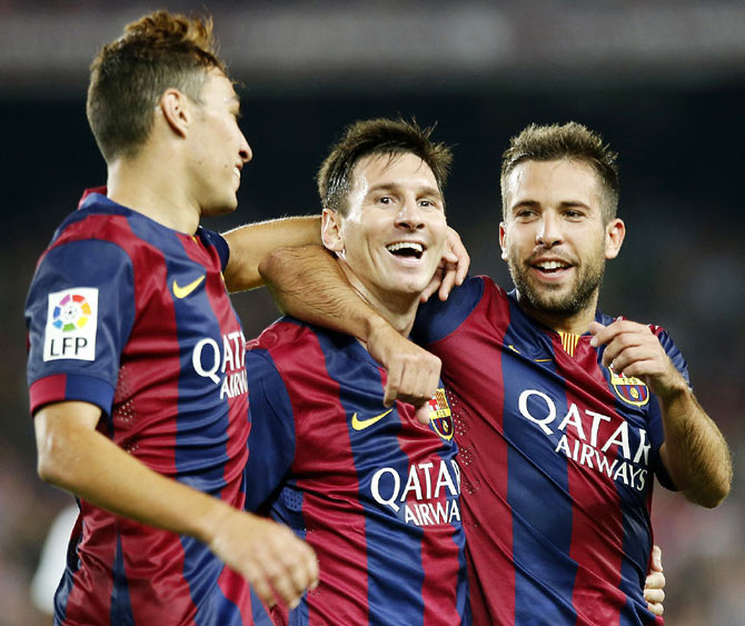 Barcelona's Lionel Messi (centre) celebrates his second goal with teammate Munir El Haddadi (left) and Jordi Alba during their Spanish first division La Liga match against Elche