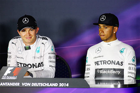 Mercedes' Nico Rosberg of Germany smiles next to teammate Lewis Hamilton of Great Britain