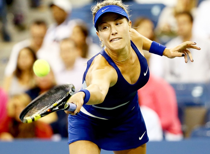 Eugenie Bouchard of Canada returns a shot against Sorana Cirstea of Romania