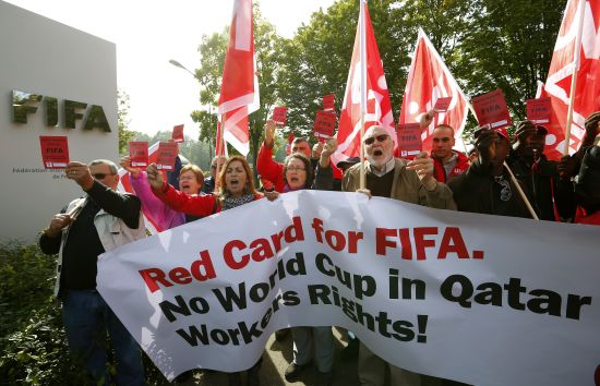 Members of the Swiss UNIA workers union display red cards