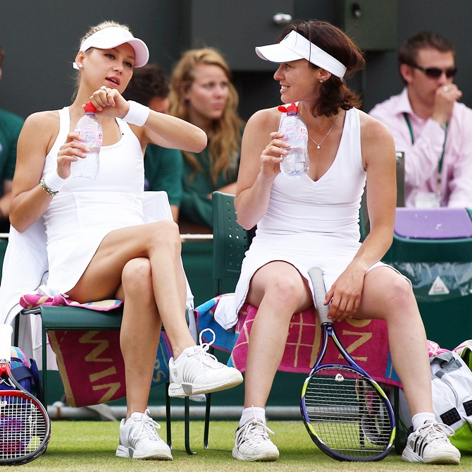Anna Kournikova of Russia, left, rests with Martina Hingis of Switzerland