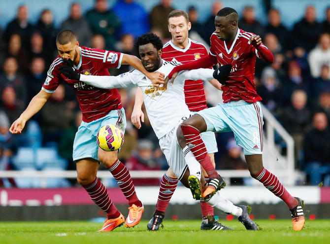 Wilfried Bony of Swansea City is closed down by West Ham's Winston Reid (left) Kevin Nolan and Cheikhou Kouyate (right) during their match on Sunday