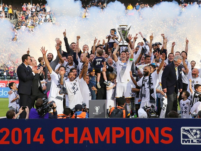 Captain Robbie Keane of the Los Angeles Galaxy hoists up the Philip F Anschutz Trophy on   the podium as his Galaxy teammates cheer on