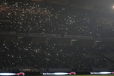 Fans stand in darkness in the tribune of the Ataturk Olimpiyat Stadium following a power outage during the Europa League Group C soccer match between Besiktas and Tottenham Hotspur, in Istanbul on Thursday