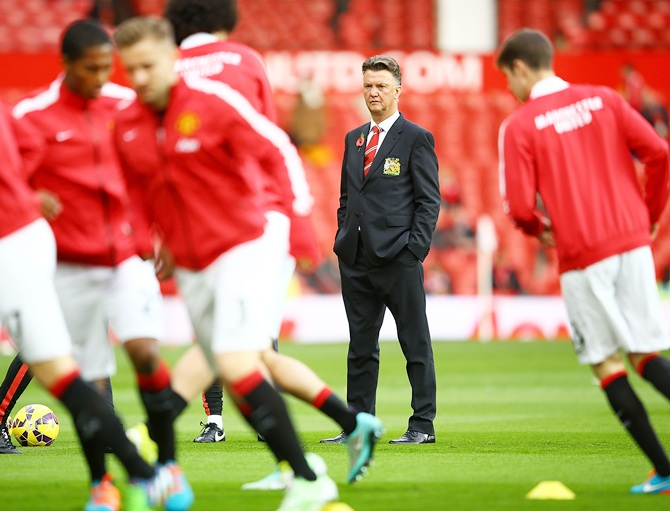 Manchester United Manager Louis van Gaal watches his players warm up