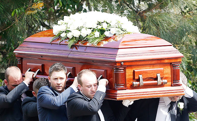 Australian Test Cricket captain Michael Clarke and Jason Hughes carry the coffin of Australian cricketer Phillip Hughes during the funeral service in Macksville, near Sydney on December 3