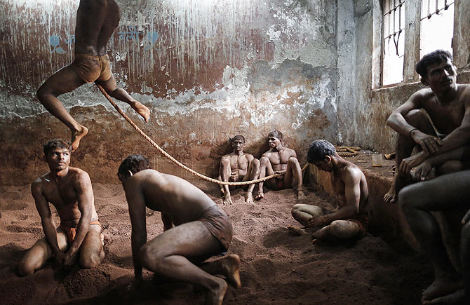 Wrestlers practise as others rest in the mud at a traditional Indian wrestling centre called Akhaara in Mumbai March 4, 2014. Kushti (mud wrestling) is a traditional sport in India but more and more young athletes are now training to wrestle on mats instead of mud to gain access to top international competitions like the Olympic Games or the Commonwealth Games.