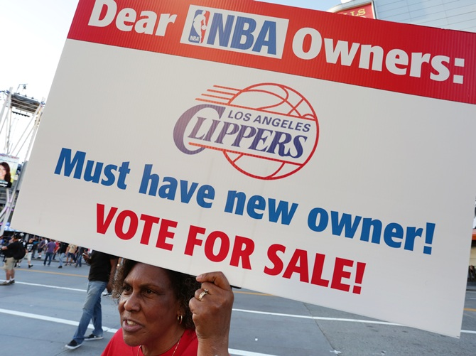 Susan Wright holds a sign protesting racist comments made by LA Clippers owner Donald Sterling