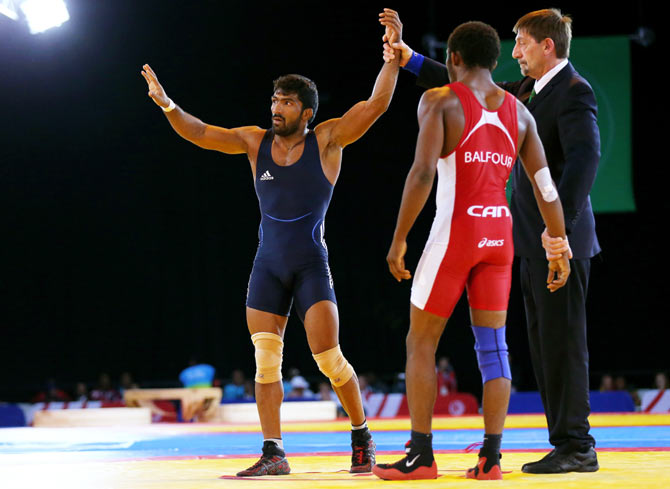 Yogeshwar Dutt (L) of India celebrates victory in the Men's FS 65 kg Gold medal match against Jevon Balfour of Canada during the Glasgow 2014 Commonwealth Games on July 31
