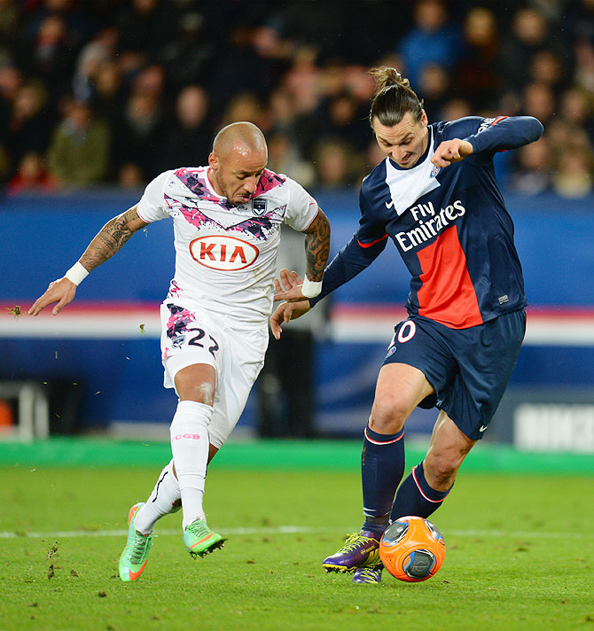 Zlatan Ibrahimovic of Paris Saint-Germain FC is challenged by Julien Faubert of Girondins de Bordeaux during their Ligue 1 match at Parc des Princes stadium in Paris on Friday