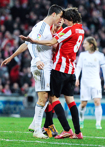Cristiano Ronaldo (L) of Real Madrid CF gets into a tussle with Ander Iturraspe of Athletic Club Bilbao during their La Liga match at San Mames Stadium in Bilbao on Sunday