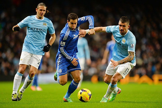 Martin Demichelis of Manchester City (left) looks on as Eden Hazard of Chelsea shrugs off a challenge from Aleksandar Kolarov of Manchester City on Monday
