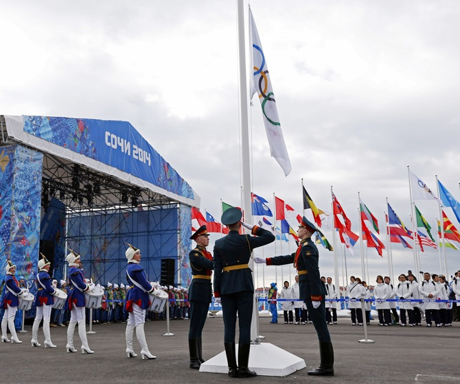 The Olympic flag is raised by Russian soldiers during the welcoming ceremony for the teams in the Athletes Village