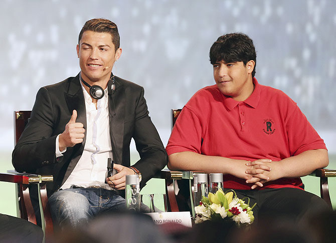 Cristiano Ronaldo (left), who plays for Real Madrid and Portugal's national soccer team, gestures as he sits next to a handicapped man, invited by conference organisers as a guest, during the eighth Dubai International Sports Conference, in Dubai on December 28, 2013