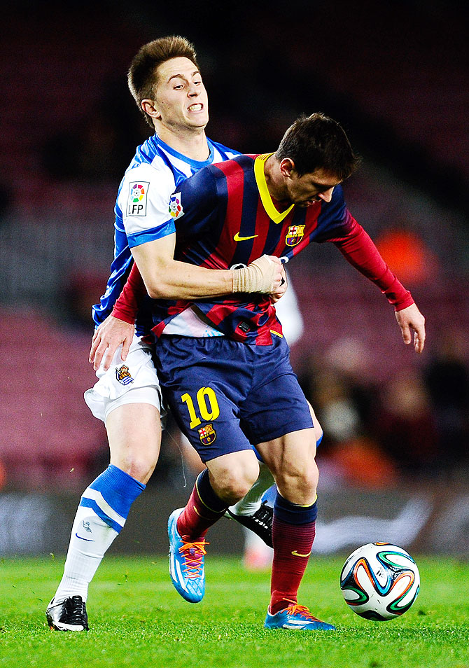 Lionel Messi of FC Barcelona is challenged by Gaztanaga of Real Sociedad during their Copa del Rey Semi-Final first leg match at Camp Nou in Barcelona on Wednesday