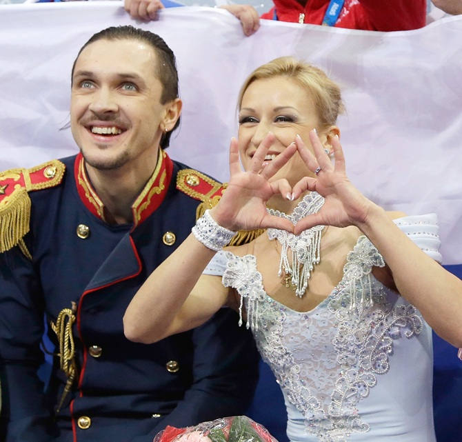 Maxim Trankov and Tatiana Volosozhar of Russia wait for their score after competing in Figure Skating