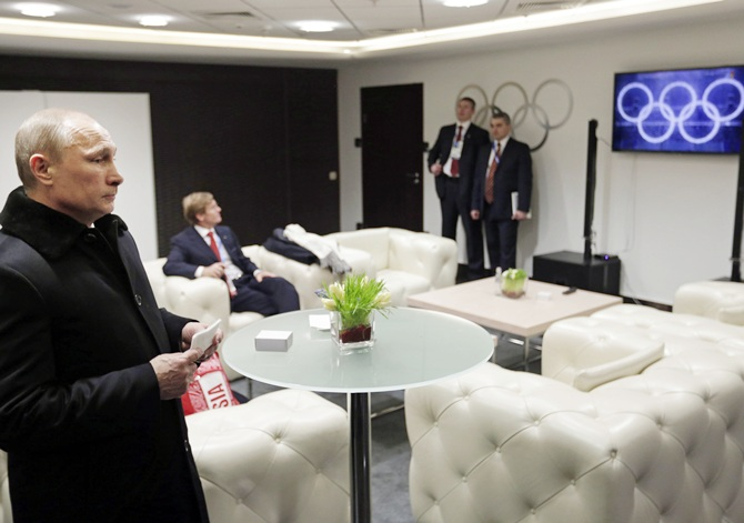Russian President Vladimir Putin (left) waits in the presidential lounge