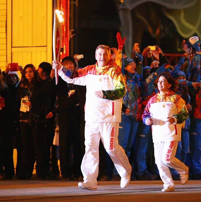 Irina Rodnina and Vladislav Tretyak approach the the Olympic cauldron as they prepare to light it