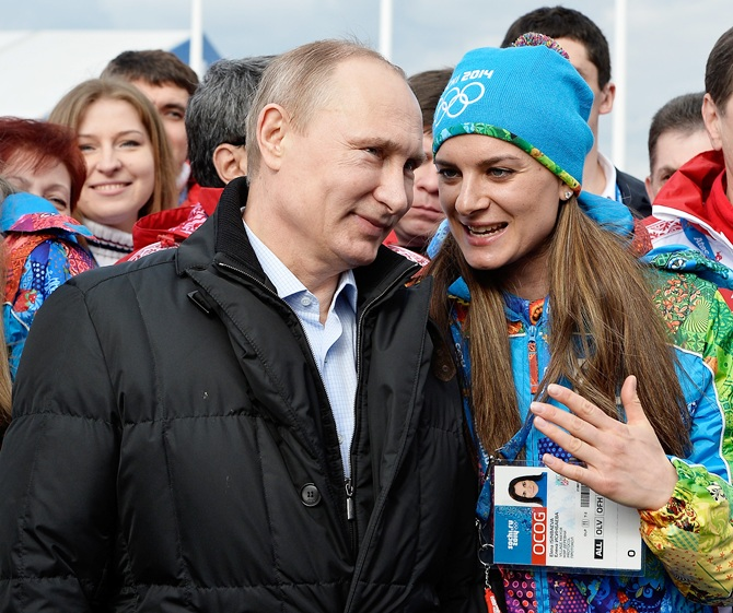 Russian President Vladimir Putin speaks with Olympic Village Mayor Elena Isinbaeva