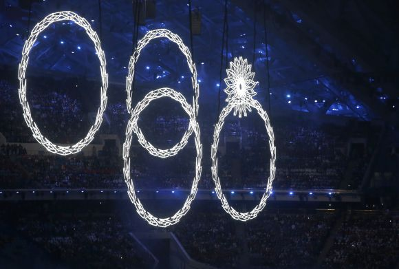 Four out of five of the Olympic rings are seen lit up during the opening ceremony