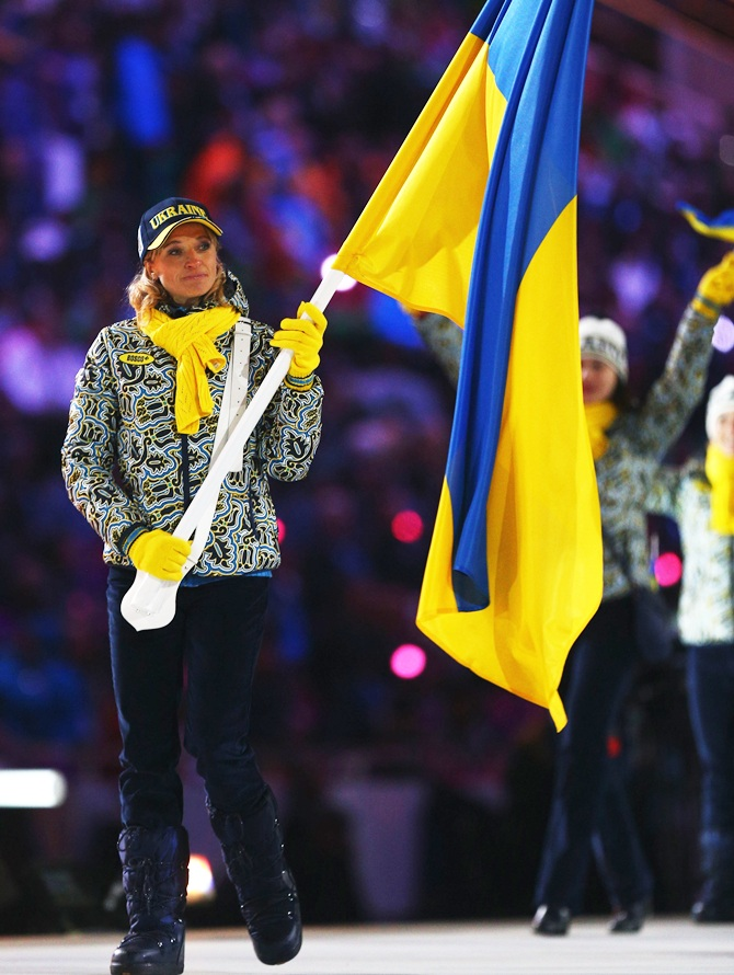 Cross country skier Valentina Shevchenko of the Ukraine Olympic team carries her country's flag.