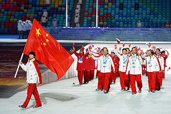 Figure skater Jian Tong of the China Olympic team carries his country's flag during the Winter Games Opening Ceremony in Sochi on Friday
