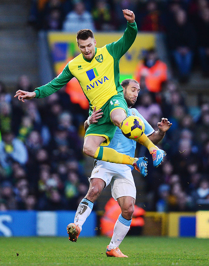 Anthony Pilkington of Norwich City (left) and Pablo Zabaleta of Manchester City vie for possession during their match at Carrow Road in Norwich on Saturday