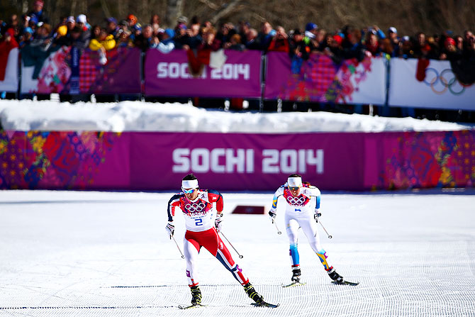 Marit Bjoergen of Norway approaches the finish line ahead of Charlotte Kalla of Sweden to win gold in the Ladies' Skiathlon 7.5 km Classic + 7.5 km Free at Laura Cross-country Ski & Biathlon Center in Sochi on Saturday