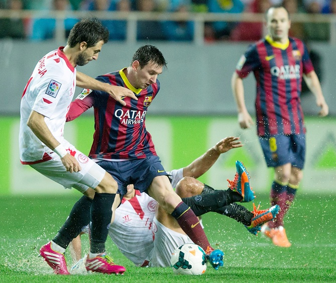 Lionel Messi, right, of FC Barcelona competes for the ball with Nicolas Pareja,left, of Sevilla FC