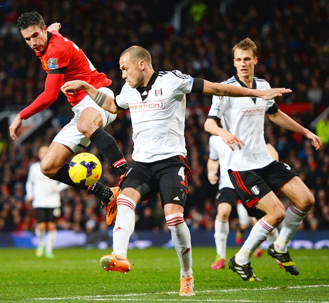 Robin van Persie of Manchester United competes with John Heitinga of Fulham