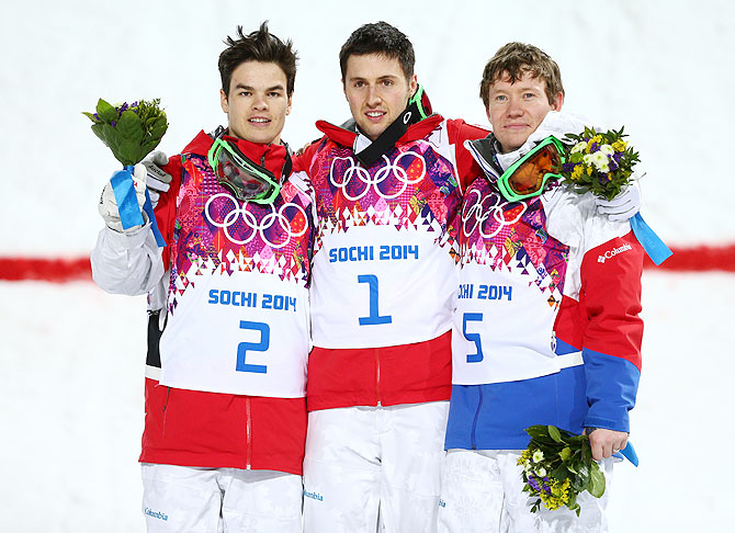 (Left-Right) Silver medalist Mikael Kingsbury of Canada, gold medalist Alex Bilodeau of Canada and Alexandr Smyshlyaev of Russia celebrate on the podium during the flower ceremony after the Men's Moguls final of the Sochi 2014 Winter Olympics at Rosa Khutor Extreme Park on Monday