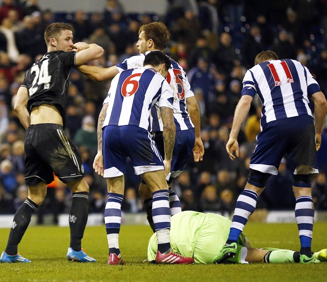 Chelsea's Gary Cahill,left, reacts as West Bromwich Albion's Ben Foster lies on the ground after the final whistle.