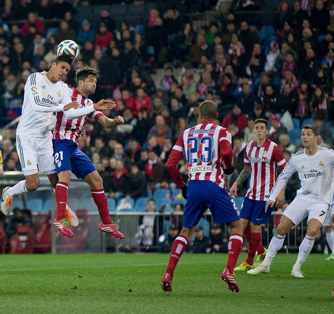 Raphael Varane of Real Madrid CF wins the header after Diego Ribas of Atletico de Madrid.