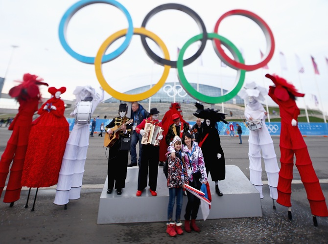 Fans take pictures in front of the Olympic rings during day four of the Sochi 2014 Winter Olympics.