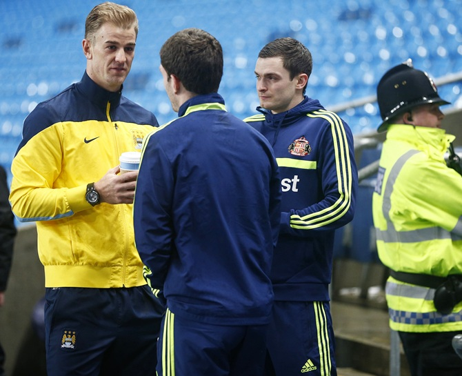 Manchester City's Joe Hart,left, talks to Sunderland's Adam Johnson,right, and Craig Gardner after their English Premier League soccer match was called off.