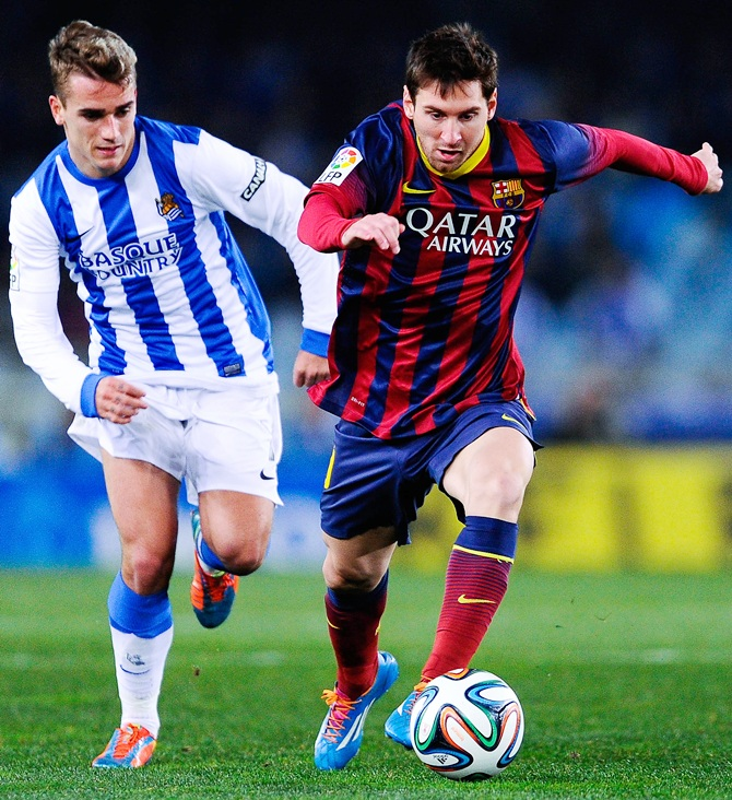 Lionel Messi of FC Barcelona runs with the ball chased by Antoine Griezmann of Real Sociedad.