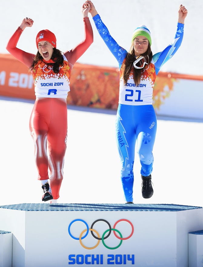 Gold medalists Dominique Gisin of Switzerland,left, and Tina Maze of Slovenia celebrateon the podium.