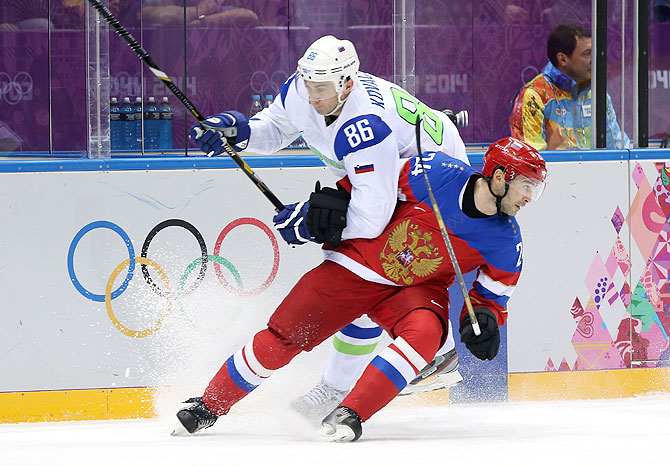 Alexander Popov #24 of Russia skates against Sabahudin Kovacevic #86 of Slovenia in the third period during the Men's Ice Hockey Preliminary Round Group A game at Bolshoy Ice Dome in Sochi on Thursday