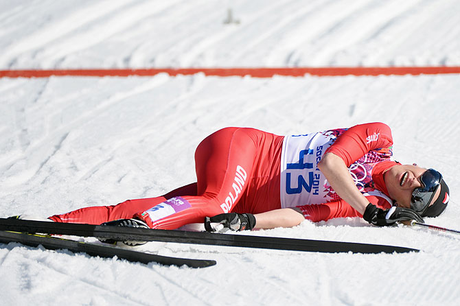 Justyna Kowalczyk of Poland collapses at the finish line first in the Women's 10 km Classic at Laura Cross-country Ski & Biathlon Center in Sochi on Thursday