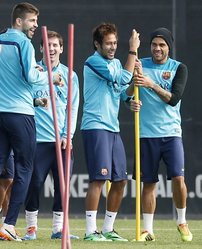 From left, Barcelona's players Gerard Pique, Lionel Messi, Neymar and Dani Alves joke during a training session.